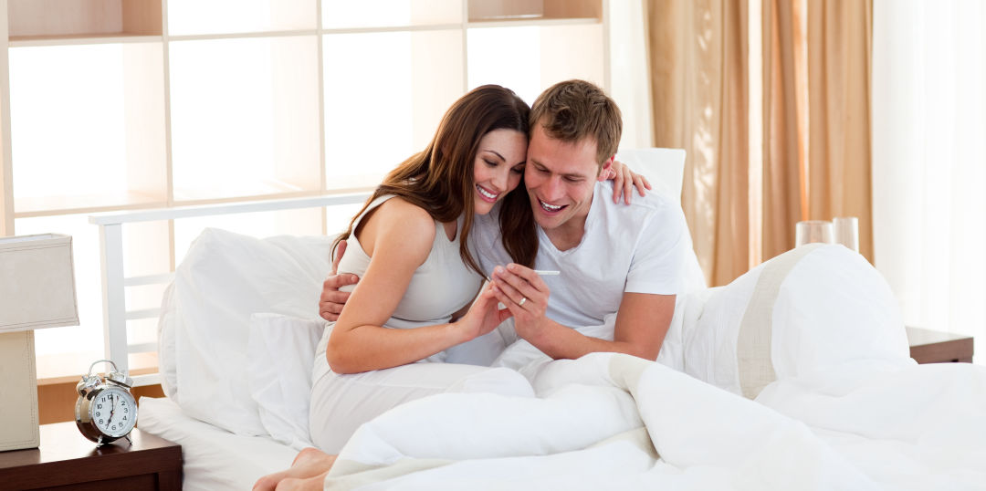 Does acupuncture help fertility? Image of a couple looking at a positive pregnancy test