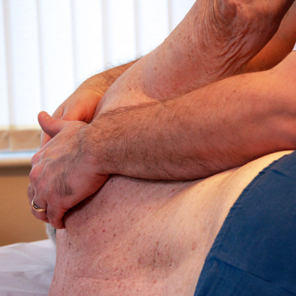 Osteopath treating upper back pain